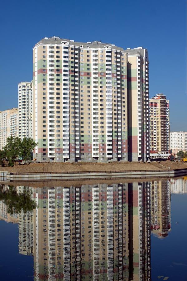 Konstruerat flerbostadshus över blå himmel för flod och för frikänd i sommardag royaltyfri foto