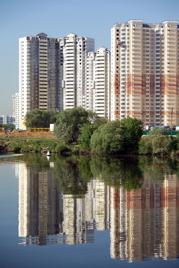 Konstruerat flerbostadshus över blå himmel för flod och för frikänd i sommardag royaltyfria foton