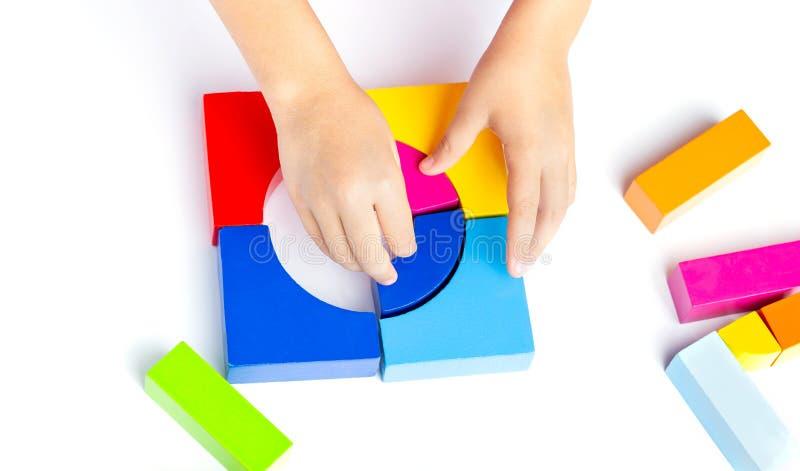 Konstruiert Kinderspiele mit farbigen Blöcken, farbige Würfel ein Modell auf weißem Hintergrund stockbild