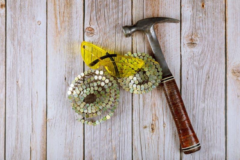 Konstrukcja okularów i gwoździ ochronnych, młotek na drewnianym tle obraz stock