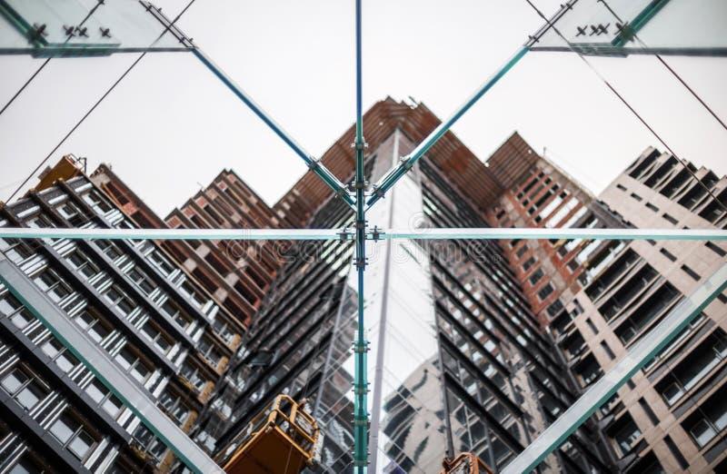 Konstrukcja szklana na tle budowanego budynku betonem i szkłem fotografia stock