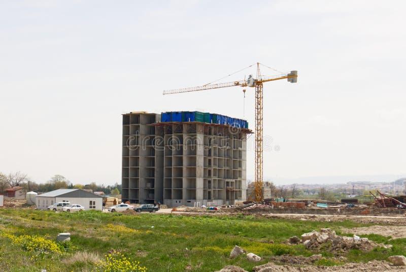 Konstruktion av byggnaden genom att anv?nda en kran arkivbild
