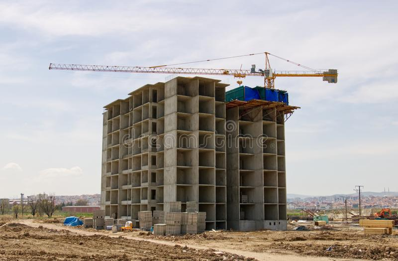 Konstruktion av byggnaden genom att anv?nda en kran fotografering för bildbyråer