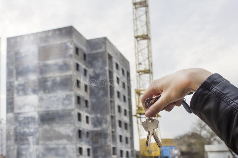 Konstruktion av ett bostads- hus, en kvinnlig hand rymmer tangenterna till lägenheten som bygger arkivfoto