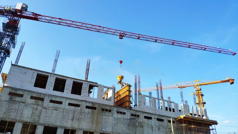 Konstruktion av ett höghus, bildandet av cementservice i fabrikstillverkade delarna till former mot en blå himmel, selektiv fokus royaltyfri bild