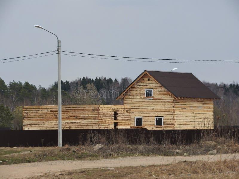 Konstruktion av ett hus som g?ras av pl?terat fan?rbr?te ramen av huset Stuga som g?ras av pl?terat tr? Uppf?rande av arkivfoto