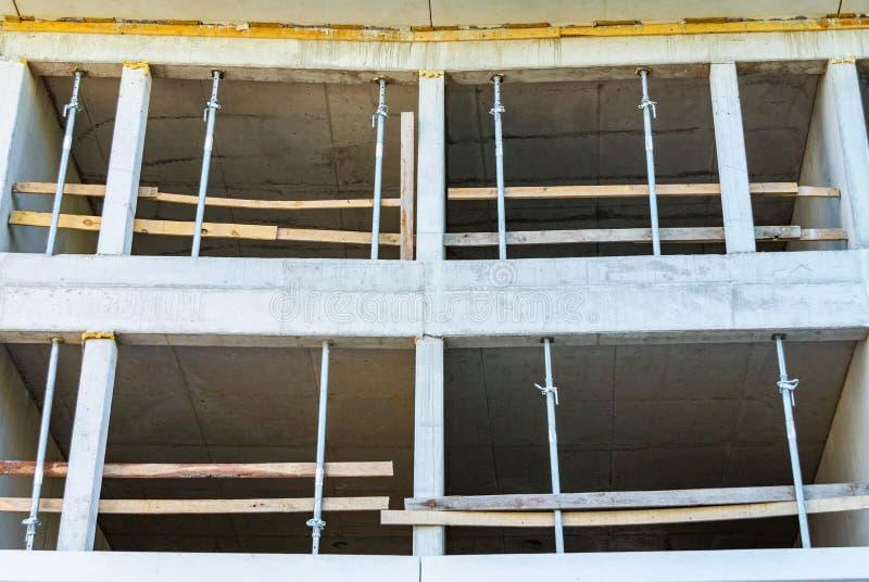 Konstruktion av ett monolitiskt hus som göras av betong, konkret service, formwork och kuggar arkivbild