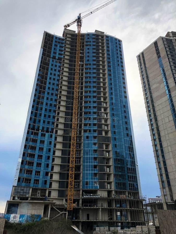 Konstruktion av ett monolitiskt ramhus, byggnad, skyskrapa av betong och exponeringsglas och gassilikatkvarter genom att använda  arkivfoton