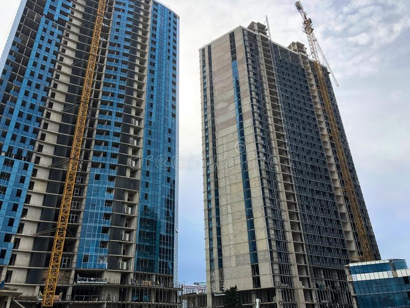 Konstruktion av ett monolitiskt ramhus, byggnad, skyskrapa av betong och exponeringsglas och gassilikatkvarter genom att anv?nda  arkivbild