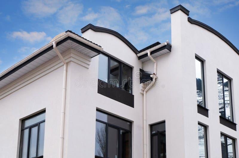 Konstruktion av ett nytt modernt hus Nyligen installerad stupränna på hustak System för stupränna för ramhus Vit avloppsränna arkivbilder