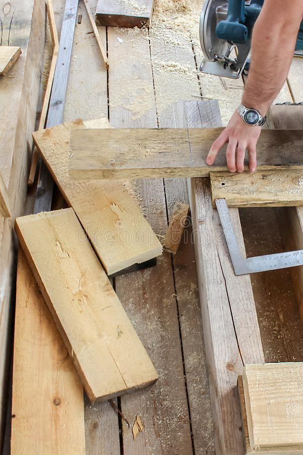 Konstruktion av ett träramhus - bräden, måttband, gon, hjälpmedel, klipp och mäta av bräden royaltyfria foton