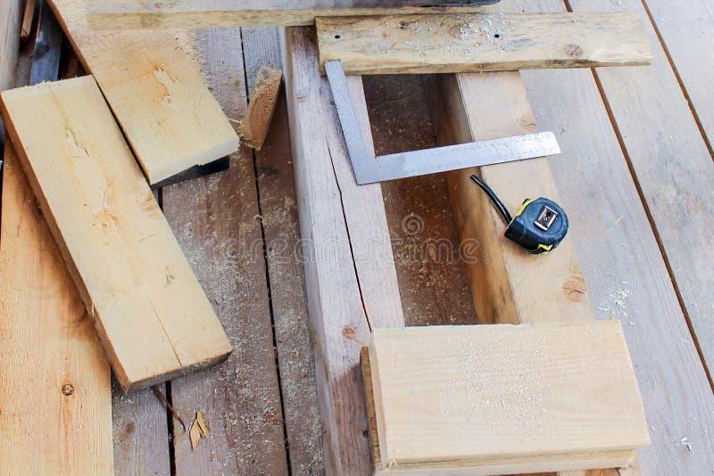 Konstruktion av ett träramhus - måttband, gon, hjälpmedel, klipp och mäta av bräden royaltyfria foton