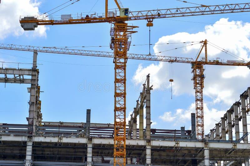 Konstruktion av höghus, tillförselen av byggnadsmaterial med hjälpen av en kran arkivbilder