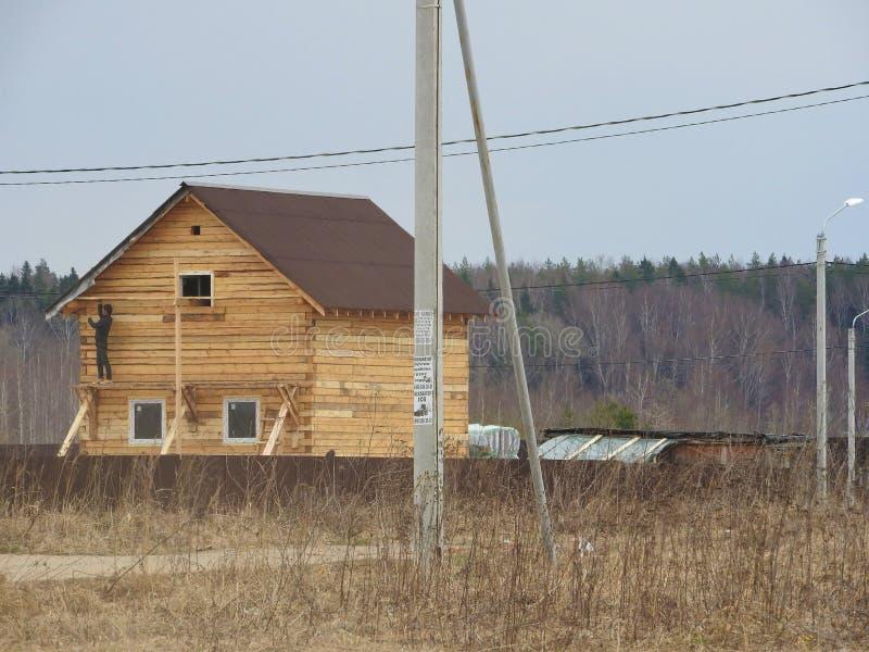 Konstruktion av huset från en stång, mannen arbetar Stugan göras av pläterat trä Installation av ramen av royaltyfria foton