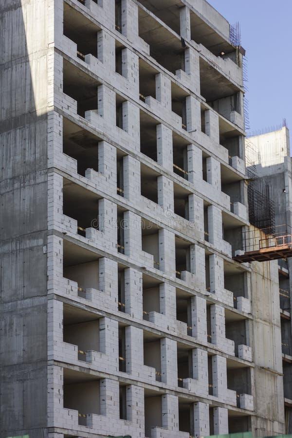 Konstruktion av mång--våning det monolitiska huset Oavslutad byggnadsfasad Begrepp av konstruktion arkivfoto