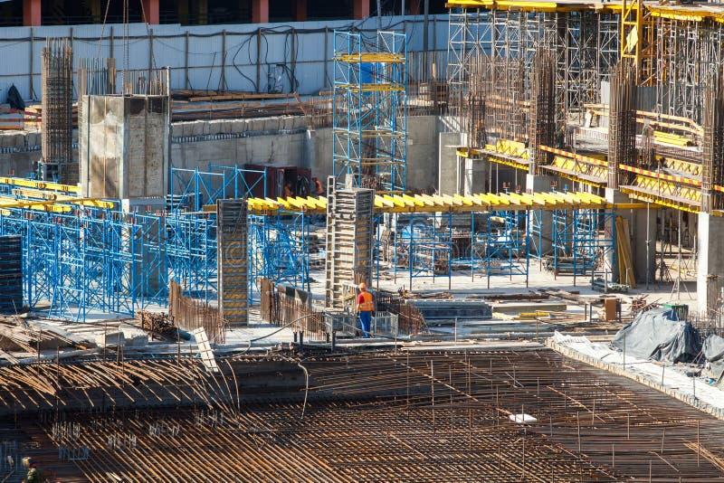 Konstruktion av stor mång--våning en kommersiell byggnad Byggmästare arbetar i overaller på den hällande cement- och betongformwo arkivbild