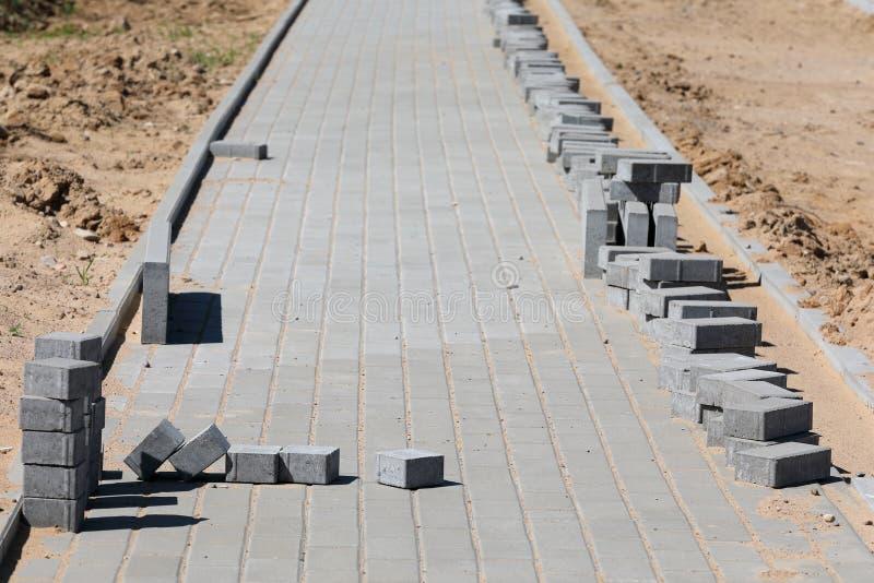Konstruktion av trottoar med konkret tegelsten arkivbild