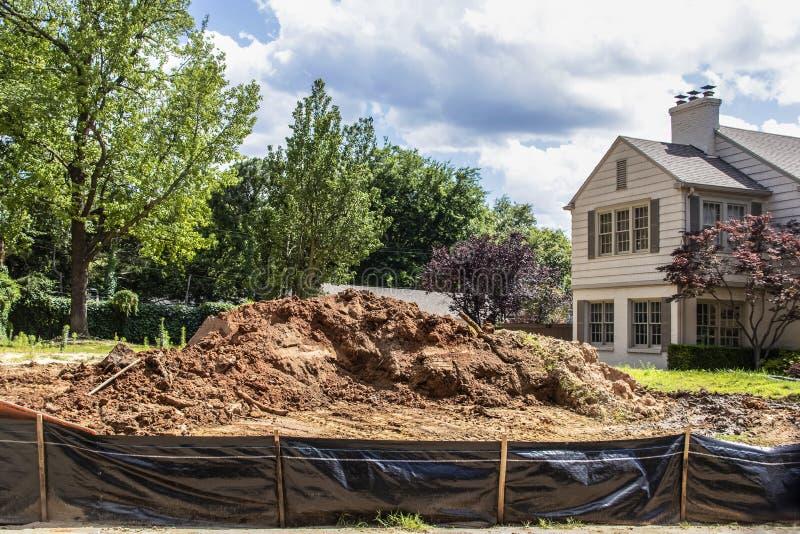 Konstruktion - hög av smuts i vakant lott bak det svarta plast- staketet i exklusiv grannskap med delar av närgränsande hus och royaltyfri fotografi