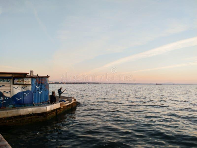 Konstruktion i stads- kostad linje, moln och det lugna havet på sumset, Thessaloniki Grekland royaltyfri fotografi