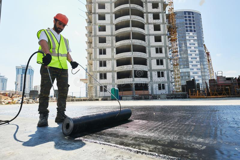Konstruktion och isolering för plant tak Värma och smältande bitumen som taklägger filt royaltyfri foto