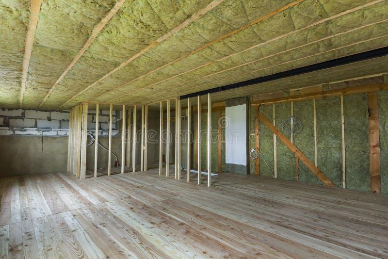 Konstruktion och renovering av stort rymligt tomt oavslutat loftrum med det ekgolvet, väggar och taket som isoleras med, vaggar u arkivbild