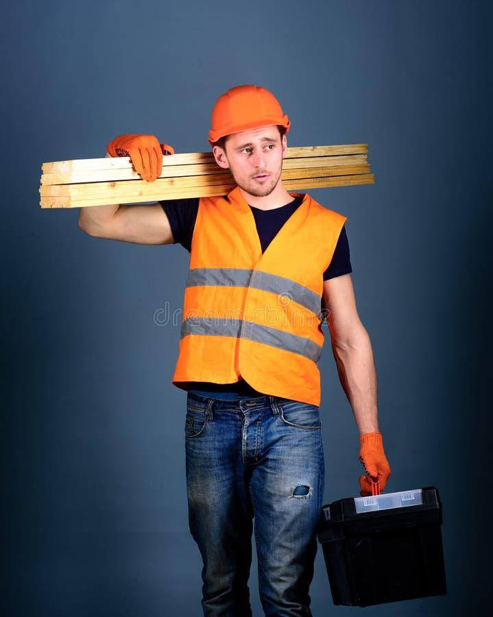 Konstruktions- och snickeribegrepp Mannen i hjälm, den hårda hatten rymmer toolboxen och trästrålar, grå bakgrund snickare arkivfoto
