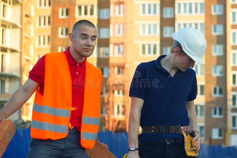 Konstruktionschef och tekniker som arbetar på byggnadsplats arkivbild