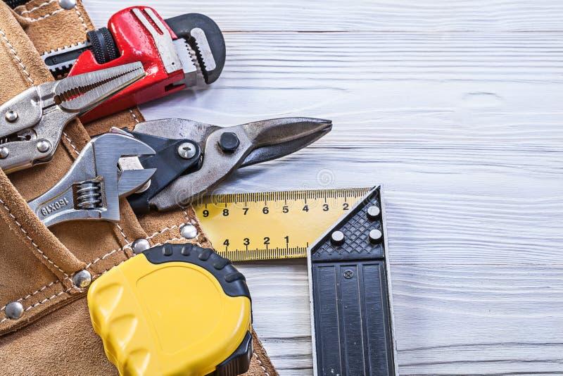 Konstruktionshjälpmedel i byggnadsbälte på träbrädeunderhåll royaltyfria bilder