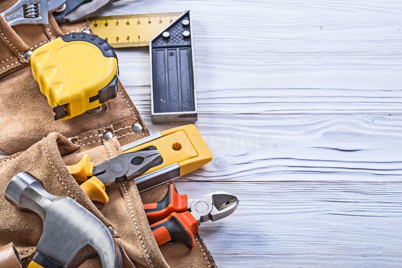Konstruktionshjälpmedel i läderbyggnadsbälte på träbrädeströmförsörjningen royaltyfria foton