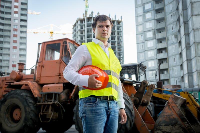 Konstruktionsinspektör som poserar bredvid grävskopan på byggnadsplats arkivfoton