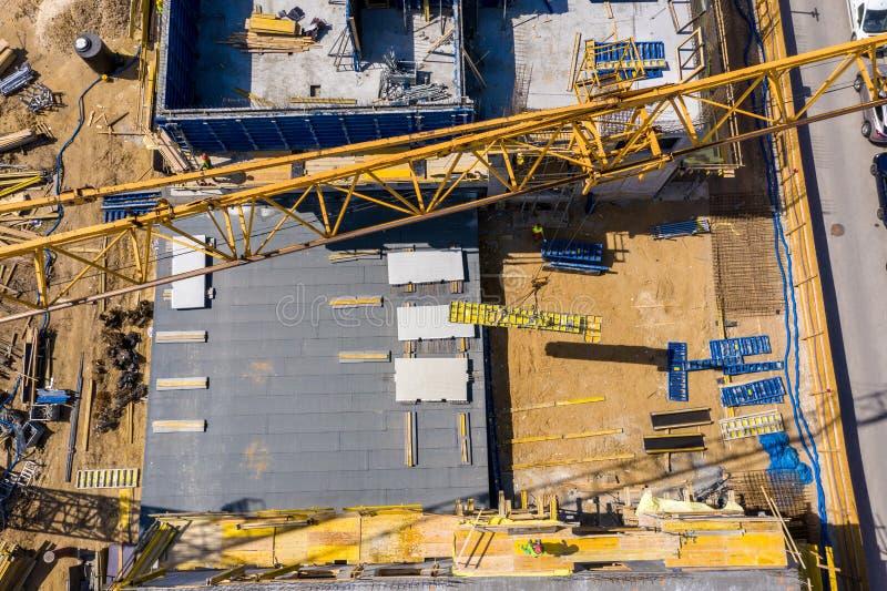 Konstruktionskran bredvid huset under konstruktion från en höjd, flyg- sikt arkivfoto