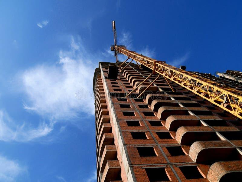 Konstruktionskran nära byggnad på bakgrund för blå himmel royaltyfri bild
