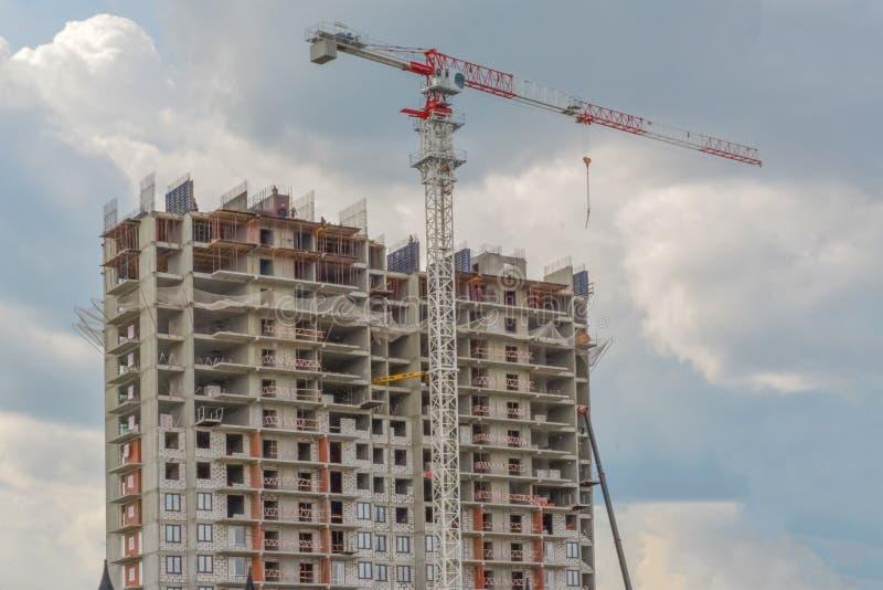 Konstruktionskran och byggnad under konstruktion mot blå himmel royaltyfri bild