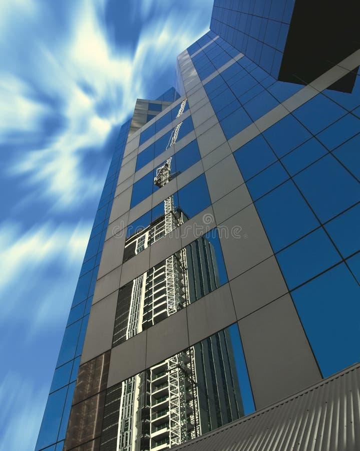 Konstruktionskran reflekterad i modern byggnad royaltyfri fotografi