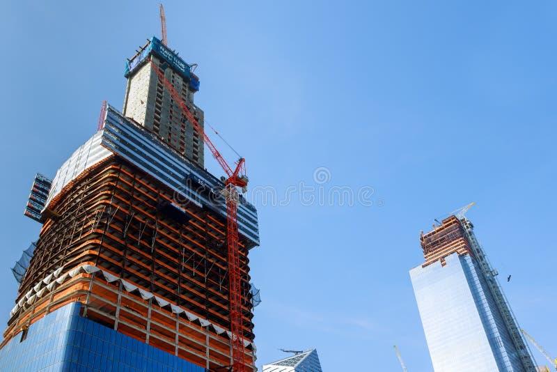 Konstruktionskranar på konstruktionsplats bygger kontorsskyskrapabyggnad i New York City på solnedgångtid royaltyfria bilder