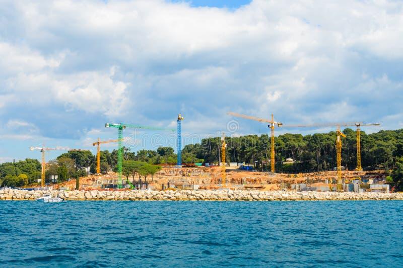 Konstruktionskranar på sjösidan som bygger en ny strandsemesterort, hotell arkivfoto