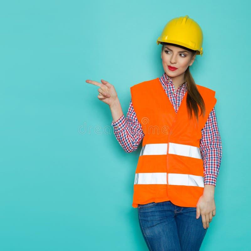konstruktionskvinnlig som pekar arbetaren royaltyfri bild
