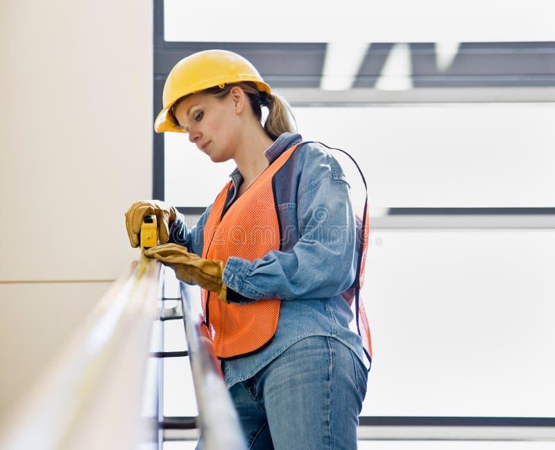 konstruktionskvinnligmätning som tar arbetaren arkivfoto