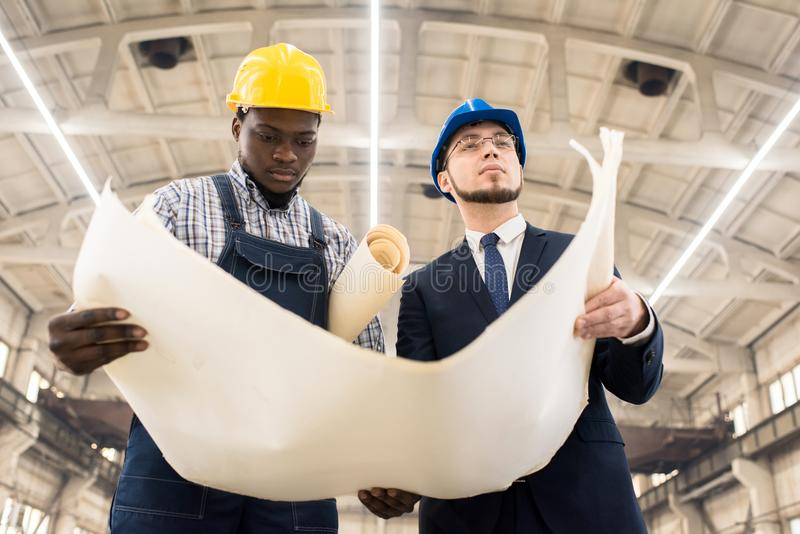 Konstruktionsleverantörer som diskuterar plan av byggnad arkivfoto