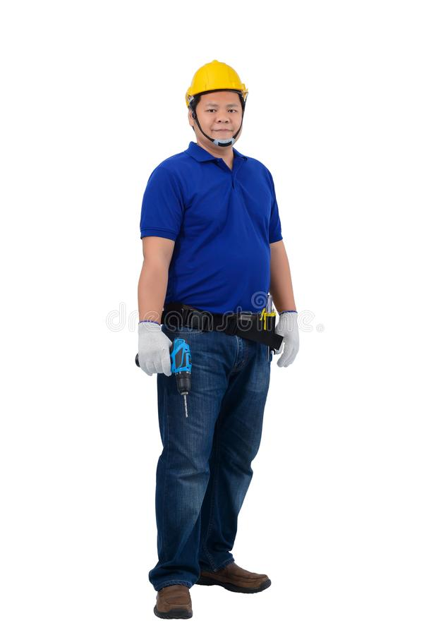 Konstruktionsmanarbetare i den blåa skjortan med skyddande handskar, hjälm med drillborren för makt för innehav för hjälpmedelbäl arkivfoton