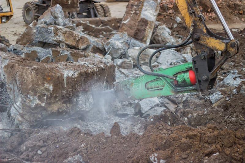 Konstruktionsmedel med den hydrauliska hammaren som bryter betong arkivfoton