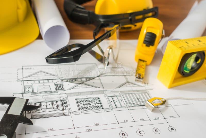 Konstruktionsplan med gula hjälm- och teckningshjälpmedel på bluep arkivfoto