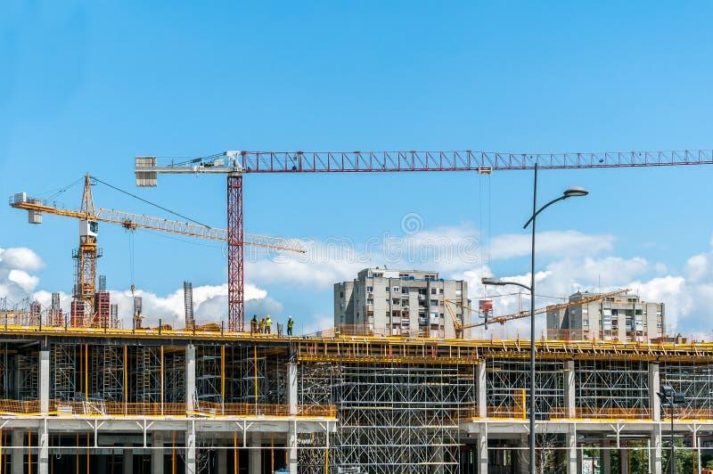 Konstruktionsplats av den nya gallerian eller köpcentret i staden med kranar maskineri, material till byggnadsställning, betong m arkivfoto