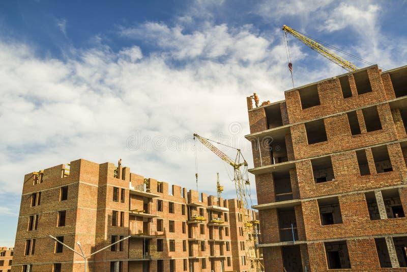 Konstruktionsplats av en hög byggnad för ny lägenhet med tornkranar mot blå himmel Bostadsområdeutveckling Fastighet p royaltyfri foto