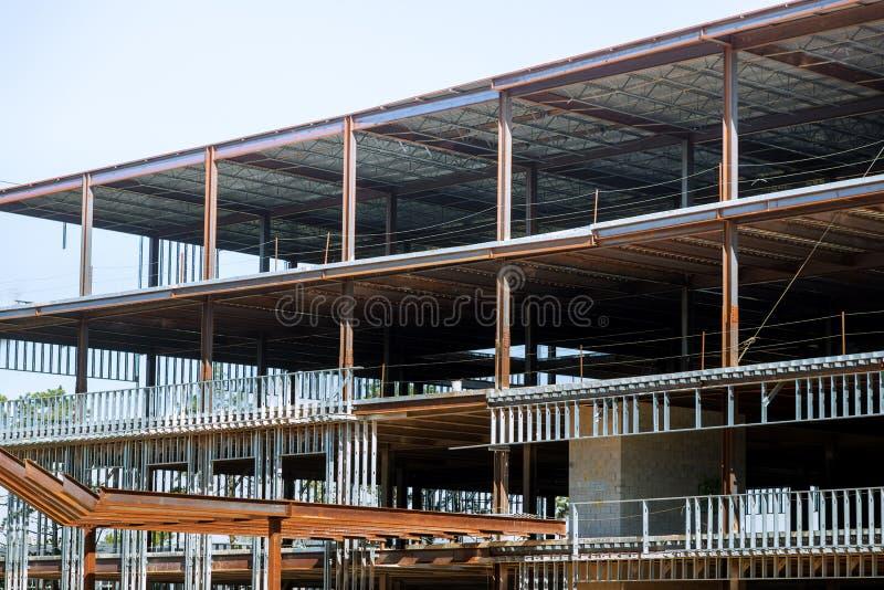 Konstruktionsplats med den byggande van vid ramen för ståldubbar i kommersiell byggnad arkivbilder