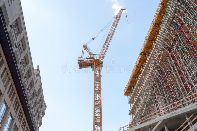 Konstruktionsplats med kranen, ställning och kontorsbyggnad och en blå himmel - Berlin 2018 arkivfoto