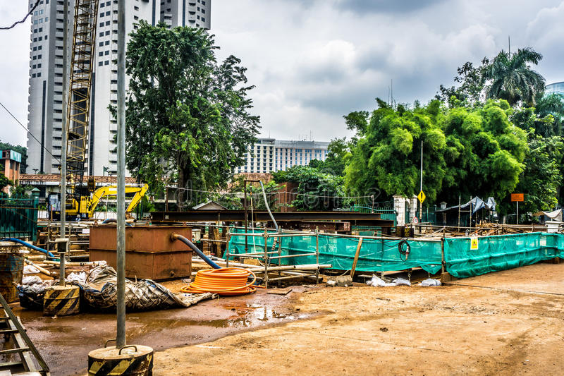 Konstruktionsplats med material och utrustningar nära det höga löneförhöjningbyggnadsfotoet som tas i Jakarta Indonesien arkivfoton
