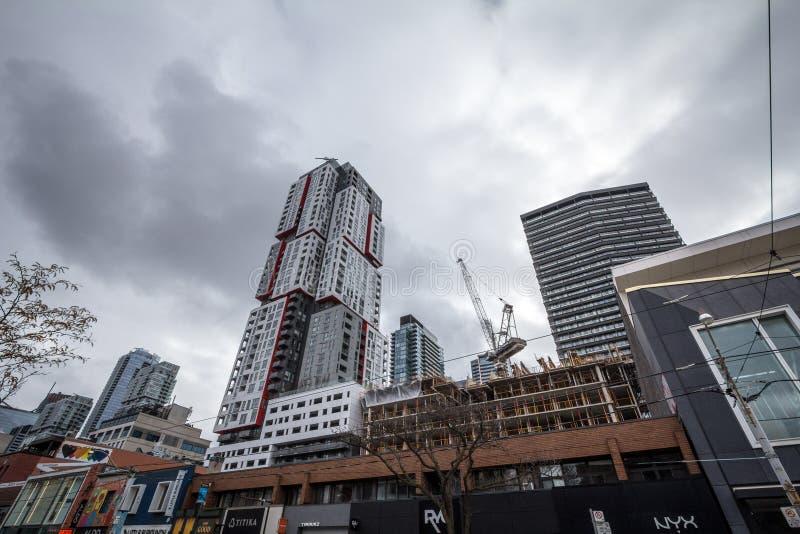 Konstruktionsplatser av torn för löneförhöjningandelsfastighethyreshus på drottninggatan, i ett område av i stadens centrum Toron royaltyfri fotografi