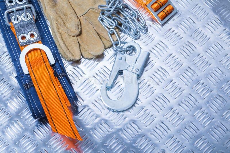 Konstruktionssäkerhetssele med handskar på det korrugerade metallarket royaltyfria bilder