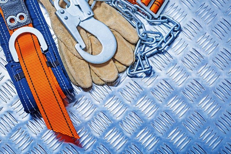 Konstruktionssäkerhetssele och handskar på det korrugerade metallarket royaltyfri bild
